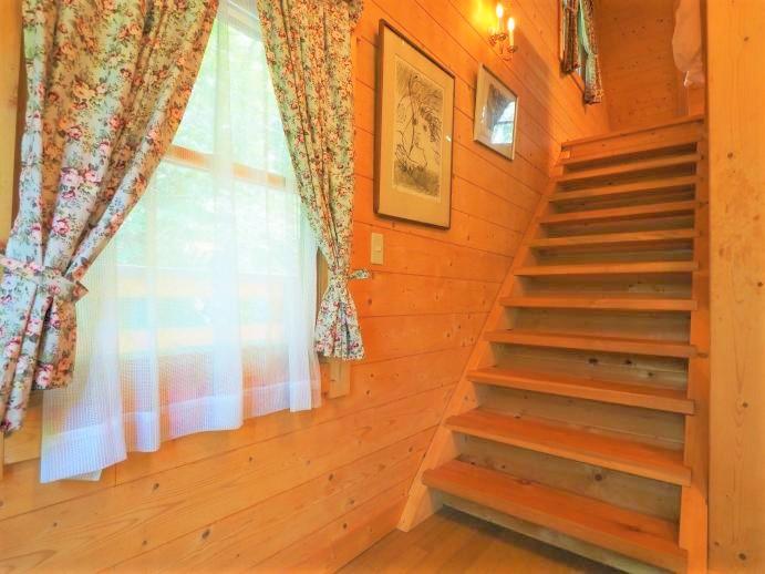 階段で二階に上がります。壁掛けの照明ランプなども素敵なもの。