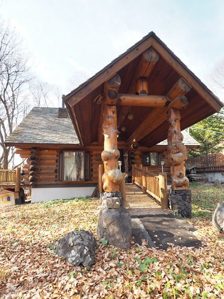 こぶ付きの丸太と浅間石の野性的な玄関アプローチ。